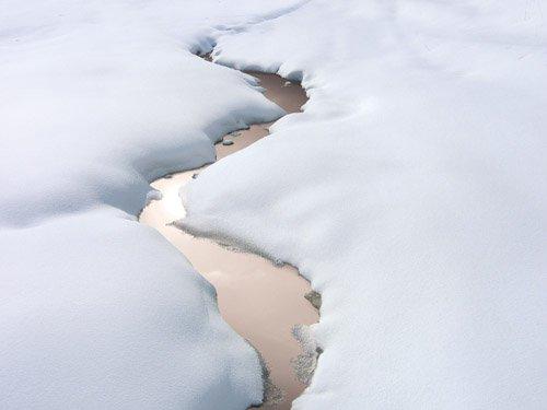 Ruisseau cuivré ondulant sous la neige à Nothalten